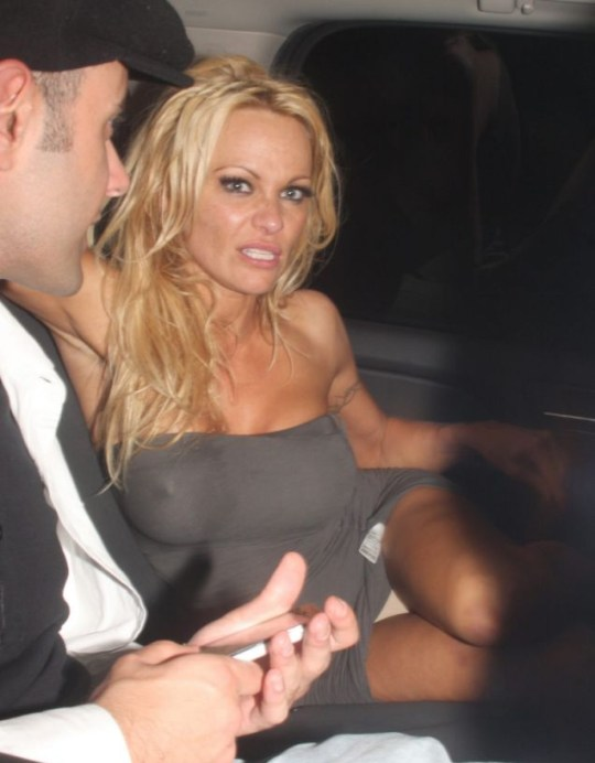 A drunk Pamela Anderson shows off her knickers to the waiting paps