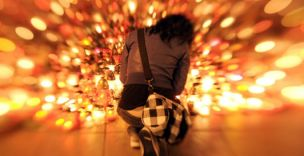 A woman mourns in front of a sea of candles laid out in front of the presidential palace