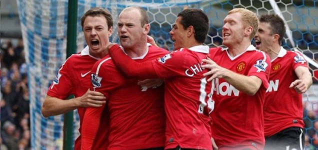 Red rule: United players mob Wayne Rooney after he netted the equaliser at Blackburn which clinched their record 19th league title