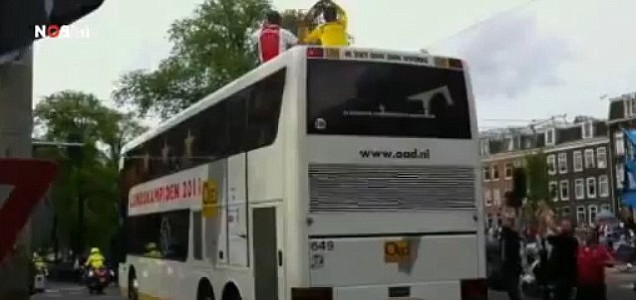Moments later Maarten Stekelenburg somehow manages to lose grip of the trophy and drop it off the top of the team bus