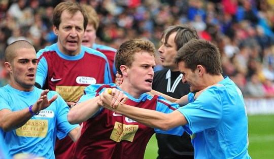 Alastair Campbell is seen looking on as a team-mate gets involved in some 'handbags' with Tom Parker of The Wanted during a charity football match