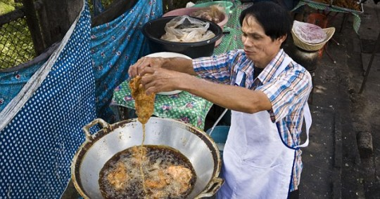 Chicken dinner: Kann Trichan shows his hands on approach to deep frying (Pic: Bronek Kaminski / Barcroft Media)