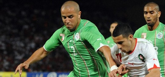 Algerian Majid Bougherra vies for the ball with Morocco's Oussama Assaidi