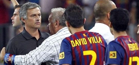 Real Madrid's coach Jose Mourinho and Barcelona players David Villa