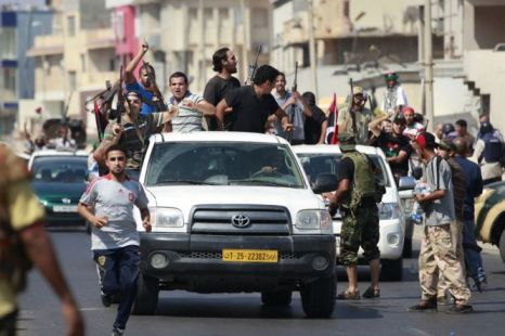 Libyan rebel fighters celebrate as they drive through Tripoli