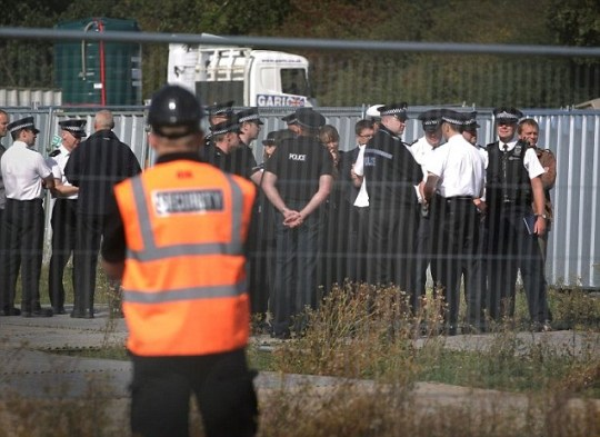 A private security guard looks on as police visit a field next to Dale Farm travellers' camp (Picture: Getty)
