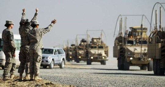 Soldiers wave to colleagues as a section of the last American military convoy to depart Iraq arrives after crossing over the border into Kuwait