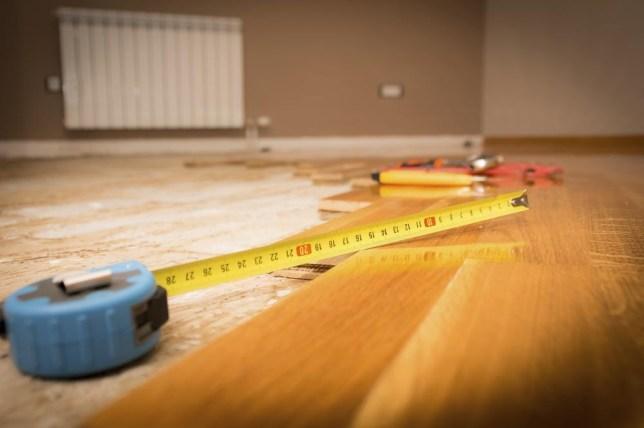 DIY hard wood flooring repair with measuring tape in view