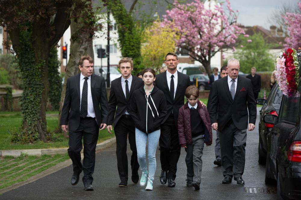 WARNING: Embargoed for publication until: 07/04/2014 - Programme Name: EastEnders - TX: 20/05/2014 - Episode: Eastenders - 4858 (No. 4858) - Picture Shows: The devastated family arrive for Lucy's funeral. Ian Beale (ADAM WOODYATT), Peter Beale (BEN HARDY), Cindy Williams (MIMI KEENE), Christian Clarke (JOHN PARTRIDGE), Bobby Beale (RORY STROUD) - (C) BBC - Photographer: Jack Barnes