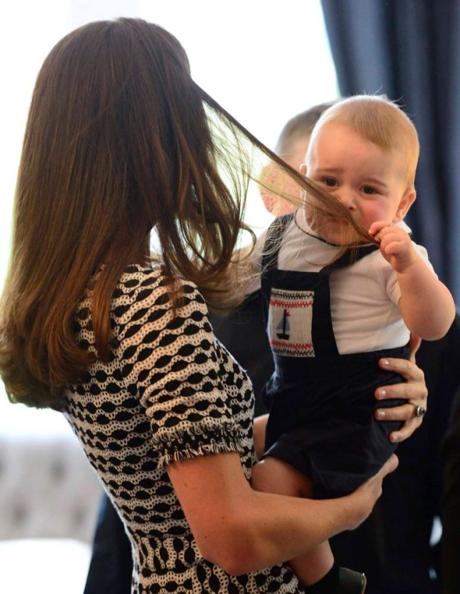 Britain's Prince George plays with his mother Catherine, the Duchess of Cambridge's hair, during a Plunket play group event at Government House in Wellington, April 9, 2014. Britain's Prince William and his wife Kate are undertaking a 19-day official visit to New Zealand and Australia with their son George. REUTERS/James Whatling/Pool (NEW ZEALAND - Tags: ENTERTAINMENT ROYALS TPX IMAGES OF THE DAY)