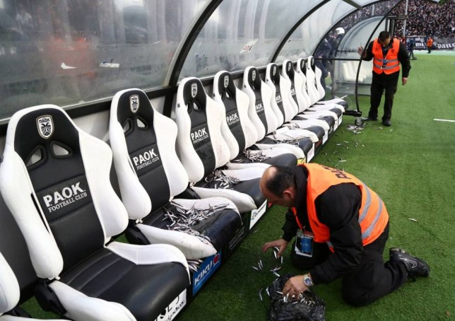 In this photo taken Wednesday, April 16, 2014 an employee of PAOK cleans Olympiakos' bench from fish before a semi-final of the Greek Cup in the northern port city of Thessaloniki. Police in Thessaloniki have arrested a PAOK fan accused of dumping a crate of fish on the visiting Olympiakos bench, in a jibe that delayed a tense Greek cup semi-final for more than an hour. Another six PAOK supporters were arrested during clashes with police before and after Thursdayís match, which PAOK won 1-0 to advance on aggregate. The game was repeatedly halted by on-turf brawls, resulting in three red cards, while PAOK fans in the stands lit thousands of flares, and several were thrown on the pitch. (AP Photo/InTime Sports, Yorgos Matthaios)  GREECE OUT