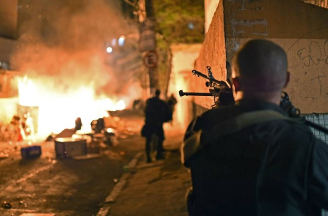 Ablaze: An armed member of Brazil's police special force takes position during the protests in Copacabana (Picture: Getty)