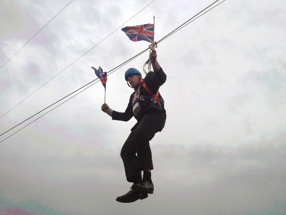 London Mayor Boris Johnson dangles in the air after getting stranded on a zip wire while trying to make a dramatic entry to a London 2012 Olympics party at Victoria Park in east London August 1, 2012. * MANDATORY CREDIT* REUTERS/Rebecca Denton/handout (BRITAIN - Tags: POLITICS SPORT OLYMPICS SOCIETY) NO ARCHIVES. FOR EDITORIAL USE ONLY. NOT FOR SALE FOR MARKETING OR ADVERTISING CAMPAIGNS. THIS IMAGE HAS BEEN SUPPLIED BY A THIRD PARTY. IT IS DISTRIBUTED, EXACTLY AS RECEIVED BY REUTERS, AS A SERVICE TO CLIENTS. MANDATORY CREDIT Handout/Reuters