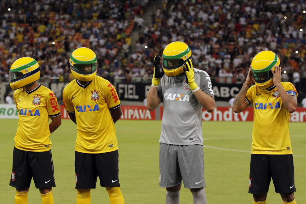 Players from the Corinthians soccer club wear replicas of the helmet worn by late Brazilian Formula One driver Ayrton Senna before the start of their Copa do Brasil match against rival club Nacional AM at the Arena Amazonas stadium in Manaus, April 30, 2014. The Corinthians paid tribute to Senna on the eve of the 20th anniversary of his death during an F1 race in Imola, Italy. REUTERS/Bruno Kelly (BRAZIL - Tags: SPORT MOTORSPORT OBITUARY TPX IMAGES OF THE DAY F1 SOCCER)