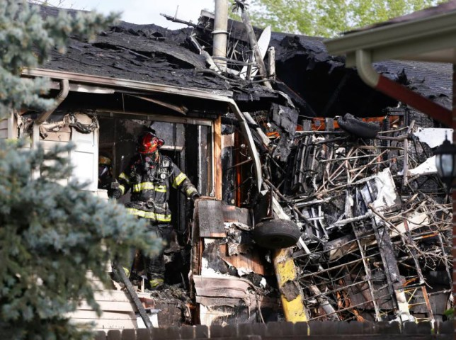 A firefighter looks for hotspots in the debris after his team put out a fire at the scene where a small plane crashed into a home in Northglenn, Colo., Monday, May 5, 2014. The plane had been towing an advertising banner and crashed into an unoccupied house in the area north of Denver, setting the plane and the house on fire. The pilot walked away with minor injuries, according to authorities. (AP Photo/Brennan Linsley)