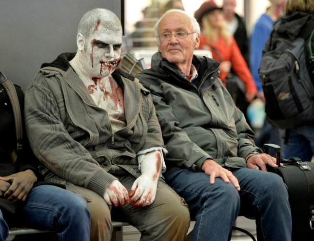 A passenger who dressed as a zombie for Halloween causes a stir at Essen railway station in Germany.  A man looks at another wearing Halloween themed make-up at Essen railway station, western Germany, Thursday, Oct. 31, 2013.   (AP Photo/Martin Meissner)