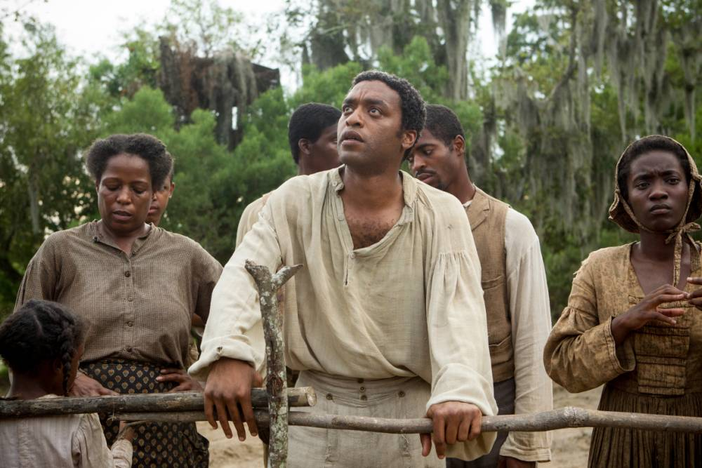 """Film: 12 Years a Slave (2013), starring Chiwetel Ejiofor as Solomon Northup.  nnnThis image released by Fox Searchlight shows Chiwetel Ejiofor, center, in a scene from the film, """"12 Years A Slave."""" Corruption tale American Hustle, digital love story Her and historic saga 12 Years a Slave are among the motion picture nominees for the Producers Guild of America announced Thursday, Jan. 2, 2014. (AP Photo/Fox Searchlight, Jaap Buitendijk)"""