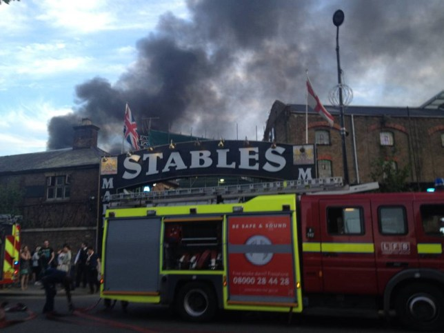 Smoke rises from the Stables Market area of Camden Town, central London on Monday, May 19, 2014. The area was evacuated by the fire services. (AP Photo, Jill Lawless)