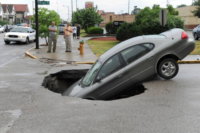 A car rests in a hole after a water main broke on Oregon St. at Main St. in Evansville, Ind. on Friday, May 30, 2014. The car's owner, rear left, said he, his girlfriend and two children were in the car at the time. All got out safely from a passenger side door. (AP Photo/The Evansville Courier & Press, Kevin Swank)