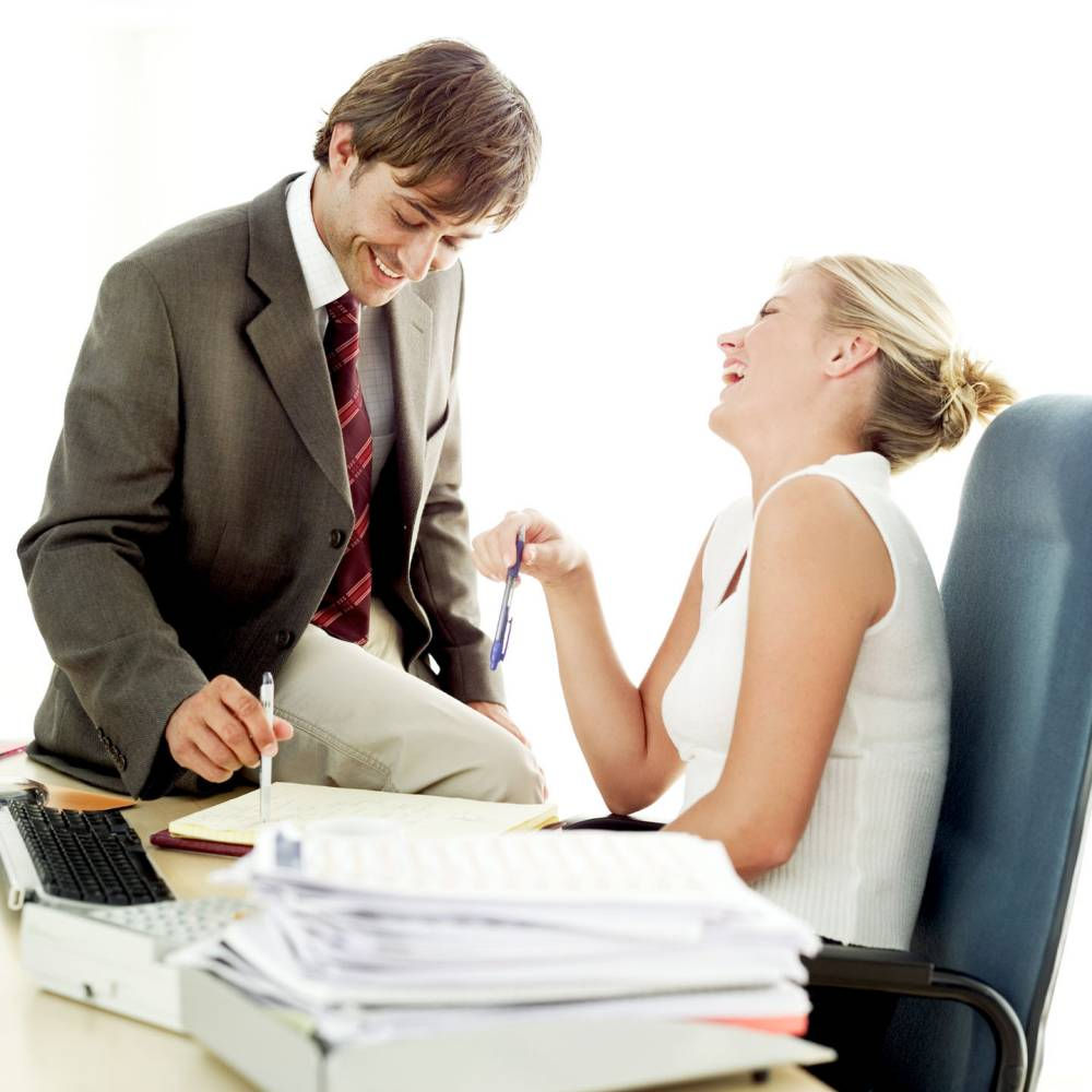 side profile of a young couple talking laughing at work enjoyment 2 25 30 years black blonde brunette caucasian colour co worker desk eye level head indoor laughing man mid adult man mid adult woman office office worker relaxing showing sitting smiling square suit two people white woman workplace highkey