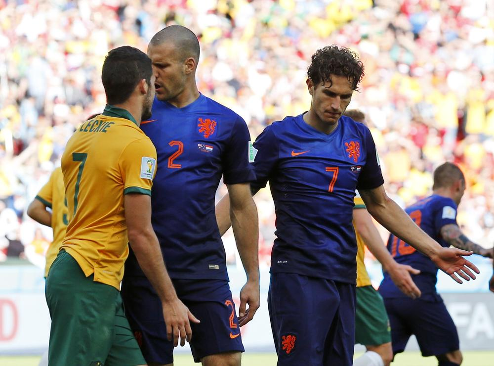 Netherlands' Daryl Janmaat tries to pull teammate Ron Vlaar (2) while he exchanges words with Australia's Mathew Leckie away from during the group B World Cup soccer match between Australia and the Netherlands at the Estadio Beira-Rio in Porto Alegre, Brazil, Wednesday, June 18, 2014. (AP Photo/Jon Super) AP Photo/Jon Super