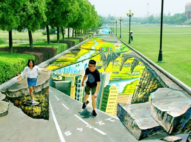 Mandatory Credit: Photo by Imaginechina/REX (3836492d)  Students pose on the worlds largest and longest 3D painting on the campus of the Communication University of China  China unveils worlds largest and longest 3D street painting on the campus of the Communication University of China in Nanjing City, China - 11 Jun 2014  The artwork, named Rhythms of Youth, is 365 meters long and 7.5 meters wide, covering over 2,600 square meters. It has set two new Guinness World Records, one for the largest, and the other for the longest street painting in the world. The team that created it was led by famous Chinese artist Yang Yongchun. It took my team more than 20 days to finish the painting on the ground, he said. Every day, we worked on it from daybreak when we could barely tell the colors apart until it was too dark to see anything. Yang also said that the painting was made in honor of the upcoming 2nd Summer Youth Olympic Games to be held in Nanjing in August. The painting includes themes from the games such as the mascot (Lele), major architectural and scenic attractions in Nanjing and the Yangtze River that runs through the city. It stretches all the way down the lane towards the end that connects to a major road. So the students on campus invariably walk towards the street art every day.