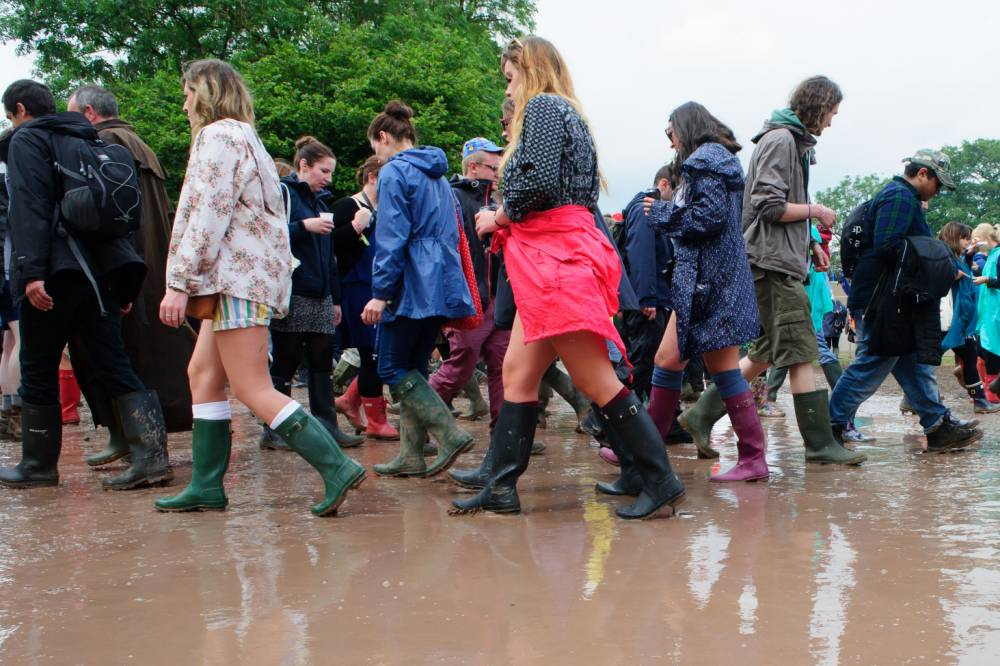 Festival goers cross an intersection near the Pyramid stage at Glastonbury music festival, England, Friday, June 27, 2014. Thousands of music fans have arrived for the festival to see headliners Arcade Fire, Metallica and Kasabian. (Photo by Jonathan Short/Invision/AP)