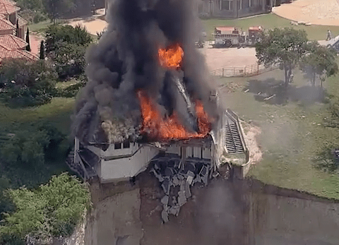Watch the moment this house is set on fire and falls off a cliff
