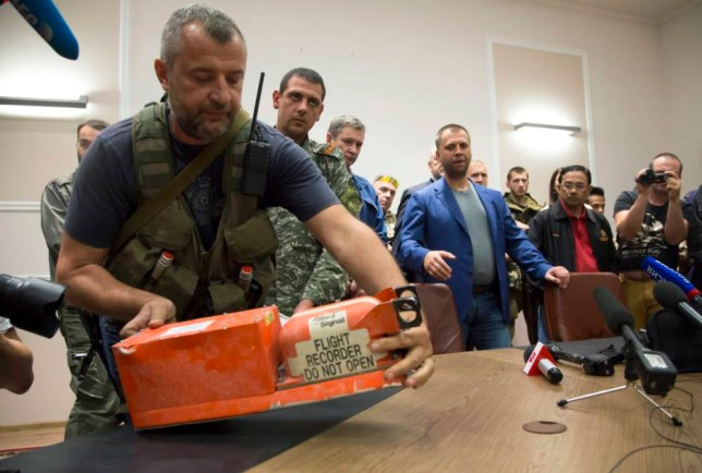 A pro-Russian fighter places a black box from the crashed Malaysia Airlines Flight 17 on a table while handing it over from Donetsk People's Republic officials to Malaysian representatives in the city of Donetsk, eastern Ukraine Tuesday, July 22, 2014. Bowing to international pressure Monday, pro-Moscow separatists released a train packed with bodies and handed over the black boxes from the downed Malaysia Airlines plane, four days after it plunged into rebel-held eastern Ukraine. (AP Photo/Dmitry Lovetsky)