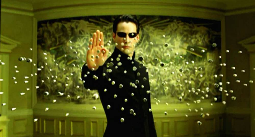 """Scene from film """"The Matrix Reloaded"""" (2003) Neo (Keanu Reeves) stops bullets in mid-air in a scene from """"The Matrix Reloaded"""". The Warner movie is scheduled for release in the UK on May 2 2003 and the US on May 15 2003. Photograph Warner Bros. Supplied by BWP Media. ...Los Angeles...California...USA"""