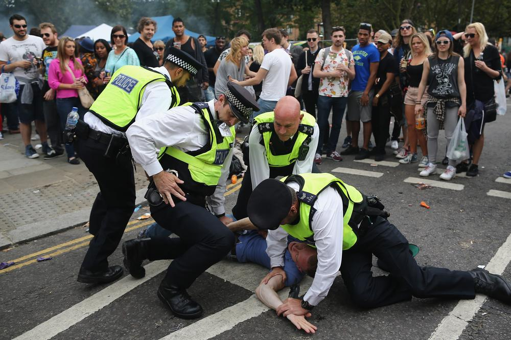 A reveller at the Notting Hill Carnival is arrested by police yesterday (Picture: Dan Kitwood/Getty)