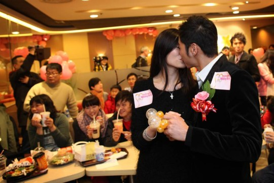 Kelvin Kwong (R) and Ashley Tse kiss during a Valentines day engagement party at a McDonald's fast food restaurant in Hong Kong on February 14, 2010. Thrown as a surprise by groom Kelvin, the function was the first of its kind for McDonald's who hope that their 'Wedding Party' will appeal to loved-up couples looking for a bride with their Big-Mac. For around 1,300 USD, potential customers can expect food and music provided for up to 50 guests.  AFP PHOTO / ED JONES (Photo credit should read Ed Jones/AFP/Getty Images)