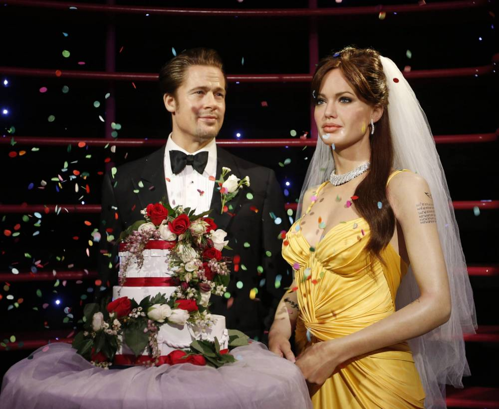 """Wax models of actors Brad Pitt and Angelina Jolie have confetti thrown on them after being presented with a wedding cake and bridal veil in celebration of their recent wedding, at the Madame Tussauds attraction in Sydney, August 29, 2014. Angelina Jolie and Brad Pitt, Hollywood's first couple, married in France over the weekend following a two-year engagement, ending nearly a decade of fevered tabloid speculation over whether """"Brangelina"""" would ever tie the knot.       REUTERS/Jason Reed    (AUSTRALIA - Tags: ENTERTAINMENT SOCIETY)"""