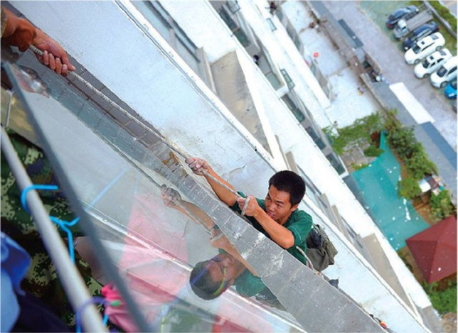 """Pic shows: Worker Liu Mail is dangling more than 80ft above the ground. Ten-year-old telly fan Tang Chu was at the end of his rope when a worker outside his family's eighth floor apartment made too much noise - so he cut their safety harness. Horrified worker Liu Mai saw the youngster run to the window and begin to slice through the rope above him and begged him to stop. He said: """"I was using an electric drill to fit security lights to the outside of the building when I felt my safety rope shaking. I looked up to see what was wrong. """"Then I saw the boy cutting the rope with a knife. I shouted at him to stop but he didn't listen and soon after, the rope was broken. I was petrified. I thought I was sure to fall, but the boy just stood and watched me."""" Liu was left dangling more than 80ft above the ground in south-western China's Guizhou province with just a single fixed rope to cling to. Workmate Zhang Pan heard his screams for help and called in firemen, who winched terrified Liu up to the 11th floor. A fire service spokesman said: """"This could have had fatal consequences. The boy didn't think about his actions. The worker was left dangling and was holding on for dear life. Luckily we were able to save the man and winch him onto a balcony to safety. """"The boy clearly thought his cartoons were more important than someone's life. He said that the builders were too loud and it was distracting him as he tried to watch his favourite cartoons. He has since apologised for his actions."""" Dad Tang Peng said: """"He just didn't think. We have apologised and bought the man a new rope. """"We also gave him a good talking too and explained what he did was very dangerous. He has promised he will not do something similar again. I think we may also need to take him for some anger management therapy."""" (ends)"""
