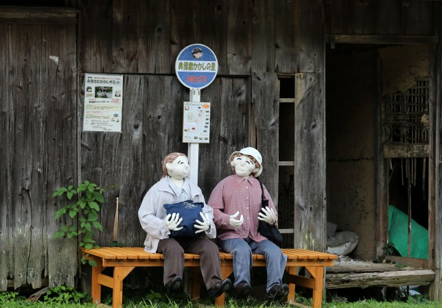 HIMEJI, JAPAN - SEPTEMBER 10: An illustration showing scarecrows sitting on a bench at a bus stand is on display at Kakashi no Sato, or the Scarecrow's Hometown on September 10, 2014 in Himeji, Japan. In this district of Yasutomi in Himeji city, over 100 of scarecrows stand in farmlands abandoned house and roadside to illustrate the good old Japanese countryside and attract visitors. (Photo by Buddhika Weerasinghe/Getty Images)