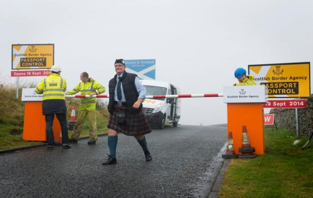 """PASSPORTS AT THE READY - A group of pranksters from both sides of the border staged the construction of a 'Scottish Border Agency' passport control centre at Carter Bar on the Scottish border near Jedburgh on the morning of Monday 15 September 2014. Alan Smith, a piper from Hawick was the first man to pass the border point ahead of it's possible opening on 19 September 2014! As the referendum race enters the home straight motorists were stunned to see the mock border control point spring up overnight. Questions remain over whether there would be a need for a border control of any sort. If Scotland goes it alone then First Minister Alex salmond has proposed to raise the nation's net immigration target. However, Yes campaigners point out that there are no border controls between Northern Ireland and the Republic of Ireland, with the Common Travel Area making for un-hindered passage. On the other hand, No campaigners have highlighted doubts over an independent Scotland's EU status and the need for border controls as part of the Schengen Agreement. """"We're not making a point for either side. We've staged this together as a group of Scots and English. We're simply united in having a laugh. Come what may, we all love a wind-up, and maybe this will give everyone a laugh and a break from the ever-increasing heat of the debate,"""" said organiser Jon Parker Lee. Photograph by Jon Parker Lee. Please credit: www.jonparkerlee.com on all usage. STANDARD FEES APPLY. PLEASE CALL IF UNCLEAR. NO SYNDICATION WITHOUT CONSENT. NO THIRD PARTY USAGE."""