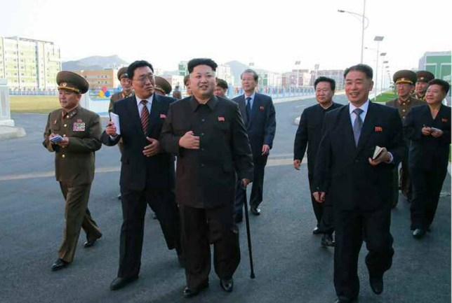 epa04445578 A photo released by the Rodong Sinmun, the newspaper of North Korea's ruling Workers Party, on 14 October 2014, shows North Korean leader Kim Jong-un (C) walking with a cane during his visit to the Wisong Scientists Residential District in Pyongyang, North Korea, 13 October 2014. Kim made his first public appearance in 40 days.  EPA/Rodong Sinmun SOUTH KOREA OUT  BEST AVAILABLE QUALITY HANDOUT EDITORIAL USE ONLY