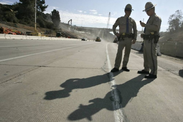 LOS ANGELES, CA -  SEPTEMBER 29:  Two California Highway Patrol officers stand in a lane of the 405 Freeway as construction crews demolish a portion of the Mulholland Drive bridge along the 405 Freeway September 29, 2012 in Los Angeles, California. The 405 Freeway is completely shut down for a 10 mile stretch this weekend for the demolition that is part of a larger $1-billion freeway improvement project. (Photo by Jonathan Alcorn/Getty Images)