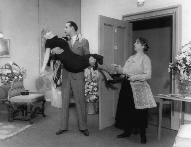 23rd March 1933:  A man lifts a young woman in his arms while an older women looks on unsympathetically in a scene from 'Gay Love' at the Lyric Theatre, London.  (Photo by Sasha/Getty Images)