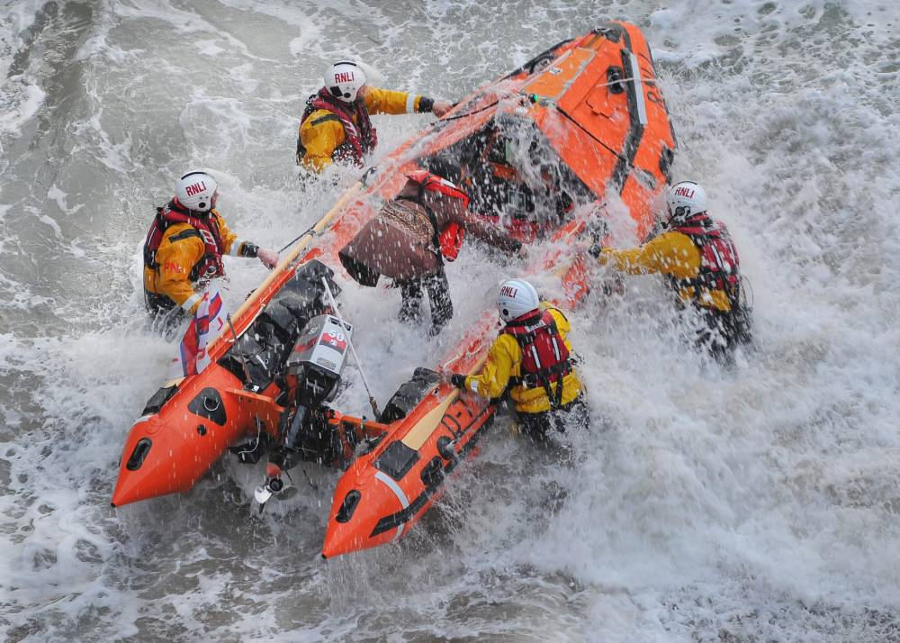 Dramatic footage shows trio being rescued from rocks after getting trapped by tide