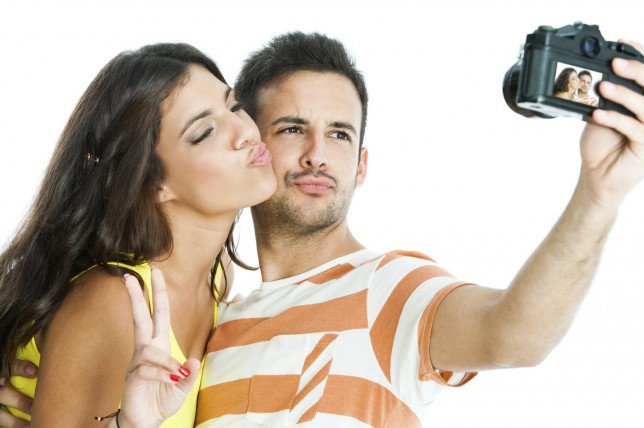 Fun portrait of cute couple taking self portrait with camera.Isolated on white background. karelnoppe/karelnoppe