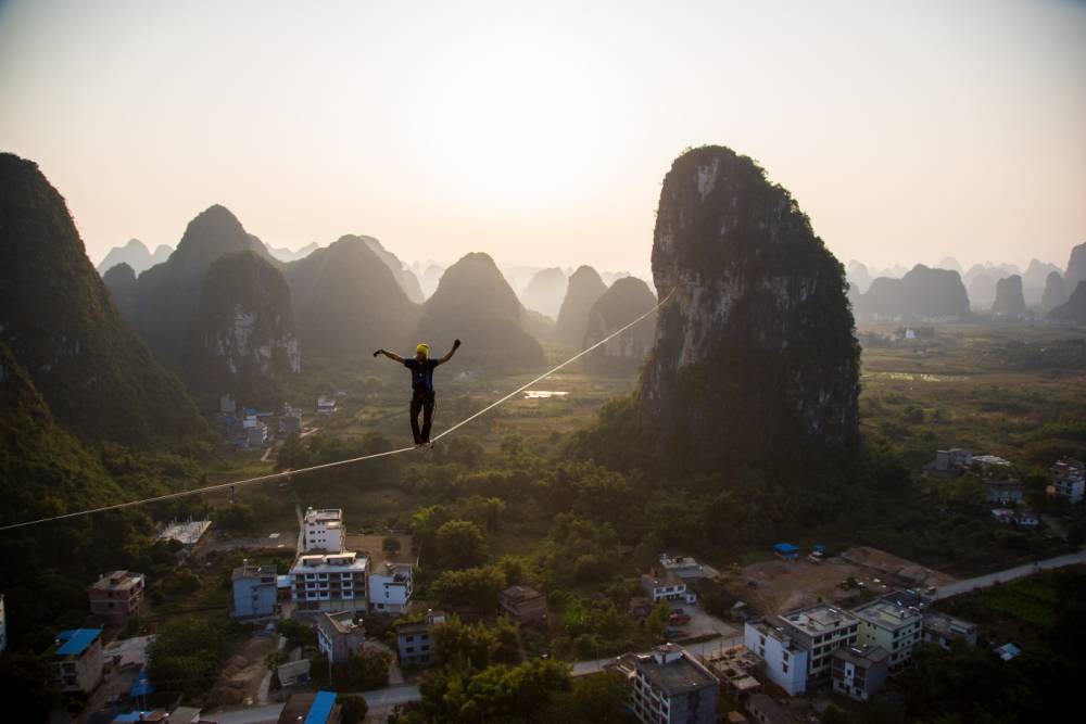 *** EXCLUSIVE - VIDEO AVAILABLE *** YANGSHUO, CHINA - NOVEMBER 25: The sun begins to set as Alexander Schulz crosses the line, on November 25, 2014, Yangshuo, China.  A DAREDEVIL has smashed the world record for longest distance walked on a highline - tiptoeing a massive 375m. The drawn-out line, which was anchored between two limestone boulders at 100m above the ground, beat the previous record by 70 metres. Alexander Schulz, 23, from Germany, spent three days trying to cross the line - falling scores of times - while battling ferocious wind and rain. Alex and his co-workers from One Inch Dreams, a slacklining company, set up the line in Yangshuo, China, where towering rocks covered in jungle foliage inspired the filmmakers of science-fiction epic Avatar. PHOTOGRAPH BY One Inch Dreams / Barcroft Media UK Office, London. T +44 845 370 2233 W www.barcroftmedia.com USA Office, New York City. T +1 212 796 2458 W www.barcroftusa.com Indian Office, Delhi. T +91 11 4053 2429 W www.barcroftindia.com