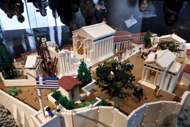 Visitors are reflected over a Lego model of the Acropolis hill, built by Australian Ryan McNaught, at the Acropolis museum in Athens December 11, 2014. REUTERS/Alkis Konstantinidis  (GREECE - Tags: SOCIETY)