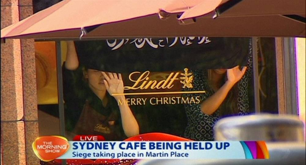This image taken from video show people holding up what appeared to be a black flag with white Arabic writing on it, inside a cafe in Sydney, Australia Monday, Dec. 15, 2014. An apparent hostage situation was unfolding inside the chocolate shop and cafe in Australia's largest city on Monday, where several people could be seen through a window with their hands held in the air. (AP Photo/Channel 7 vide AP Video) AUSTRALIA OUT