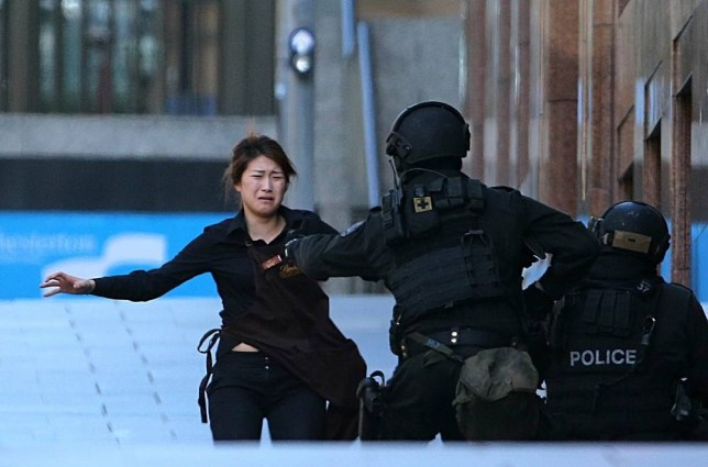 An armed tactical response police officer grabs a hostage as she runs to flee from a cafe under siege at Martin Place in the central business district of Sydney, Australia, Monday, Dec. 15, 2014. New South Wales state police would not say what was happening inside the cafe or whether hostages were being held. But television footage shot through the cafe's windows showed several people with their arms in the air. (AP Photo/Rob Griffith)