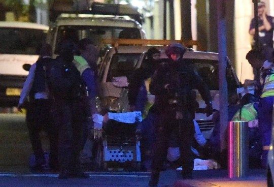 Armed Australian police engage in an operation outside a cafe in the central business district of Sydney on December 16, 2014. Police stormed the Sydney cafe where a gunman had taken hostages and displayed an Islamic flag, television footage showed early December 16. Police have confirmed the siege is over. AFP PHOTO / SAEED KHANSAEED KHAN/AFP/Getty Images