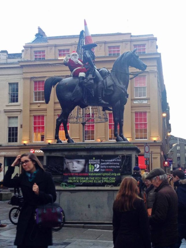 BEST QUALITY AVAILABLE A prankster, dressed in a full Father Christmas outfit sits on top of the Duke of Wellington statue on the Royal Exchange Square in Glasgow, before he was led away by police after the fire service removed him to the sound of booing from the crowd. PRESS ASSOCIATION Photo. Picture date: Wednesday December 17, 2014. See PA story POLICE Santa. Photo credit should read: Ruth Broers/PA Wire NOTE TO EDITORS: This handout photo may only be used in for editorial reporting purposes for the contemporaneous illustration of events, things or the people in the image or facts mentioned in the caption. Reuse of the picture may require further permission from the copyright holder.