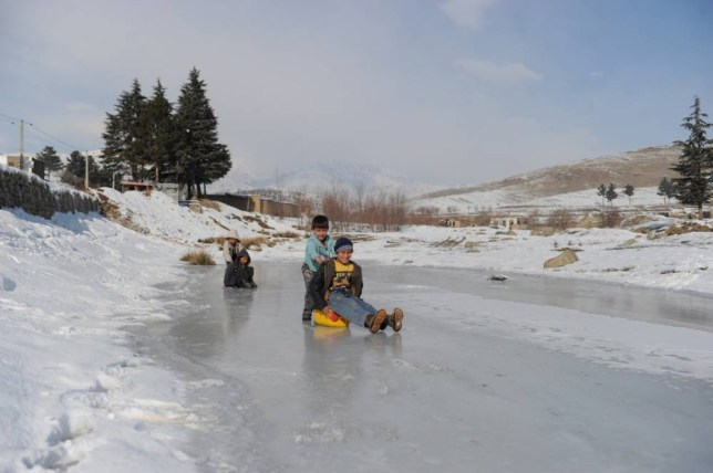 Afghan boys play on ice on the outskirts of Kabul on January 10, 2012. As winter sets in across Central Asia, many Afghans struggle to provide adaquate food and shelter for their families.  AFP PHOTO/SHAH Marai (Photo credit should read SHAH MARAI/AFP/Getty Images)