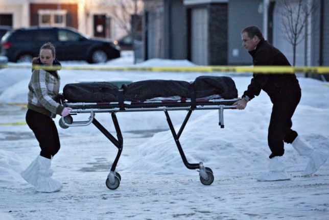 "The body of a victim is carried out of a north Edmonton home in Edmonton, Alberta, Tuesday, Dec. 30, 2014. Nine people, including seven adults and two young children, were found dead at three separate crime scenes in what Edmonton's police chief on Tuesday called a ""senseless mass murder."" (AP Photo/The Canadian Press, Jason Franson)"