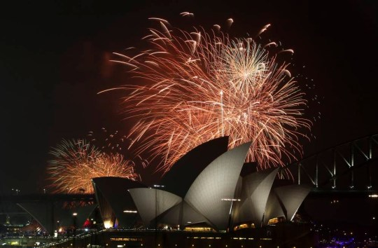 Fireworks explode over the Opera House and the Harbour Bridge during New Years Eve celebrations in Sydney, Australia, Wednesday, Dec. 31, 2014. Thousands of people crammed into Lady Macquaries Chair to watch the annual fireworks show. (AP Photo/Rob Griffith)